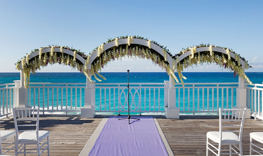 Wedding arches overlook the turquoise blue waters of the Bahamas at a destination wedding ceremony.