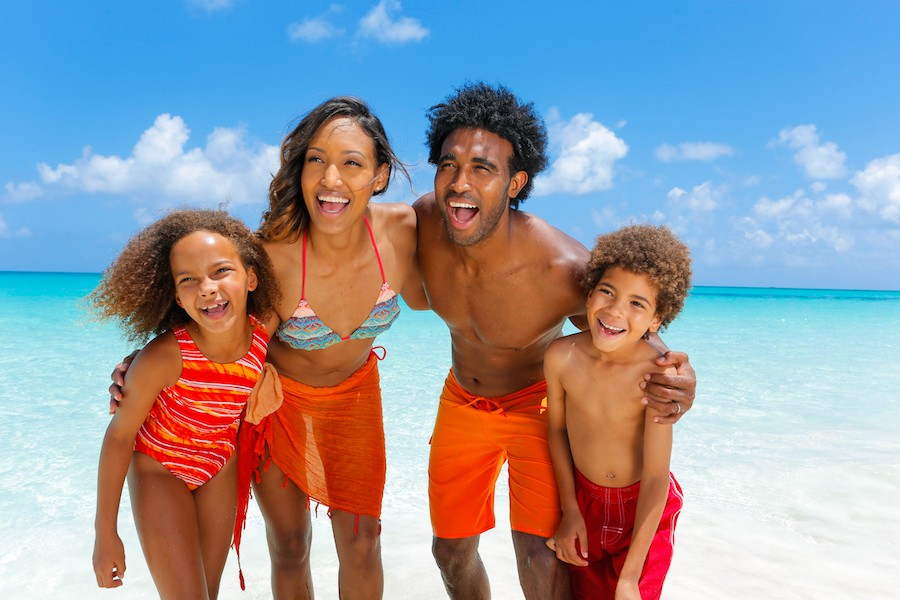 A family of four poses for a photo on the beach in Nassau Paradise Island.