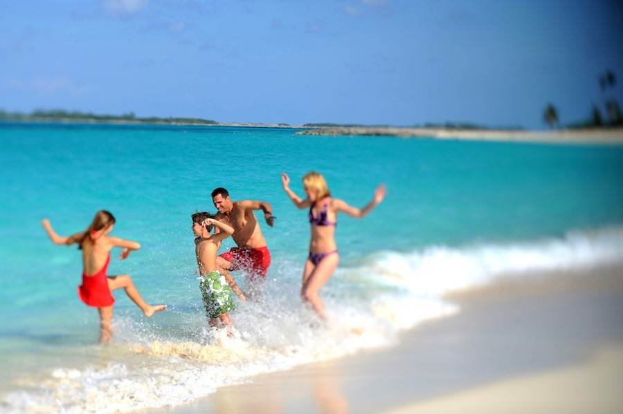 A family of four splashes in the turquoise waters of Nassau Paradise Island, Bahamas