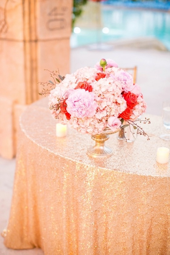 A pink floral bouquet sits on a beautiful gold tablecloth at an Atlantis wedding.