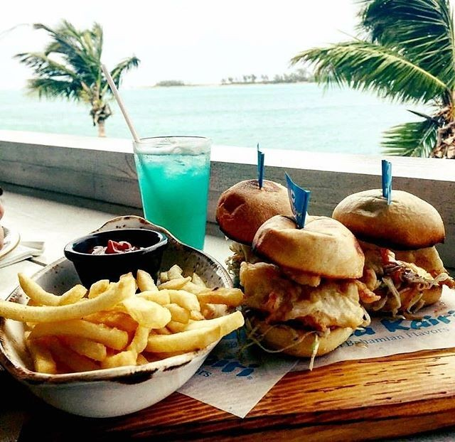 French fries, burgers and a blue icy beverage sit atop a beach-side table.