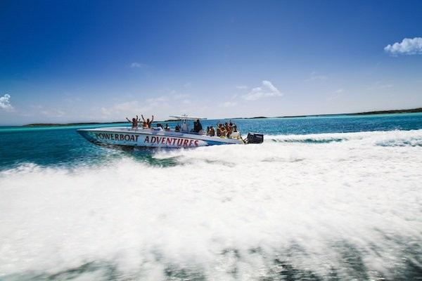 A Powerboat Adventures speed boat rides through the turquoise waters of The Bahamas.