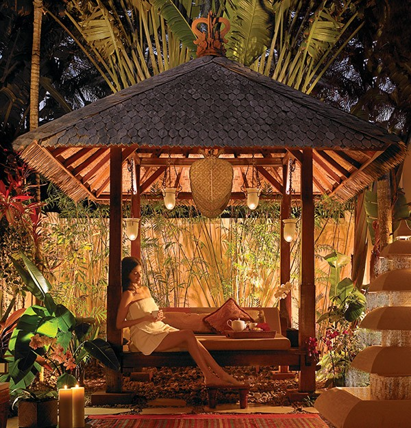 A woman relaxes in an opulent gazebo at twilight.