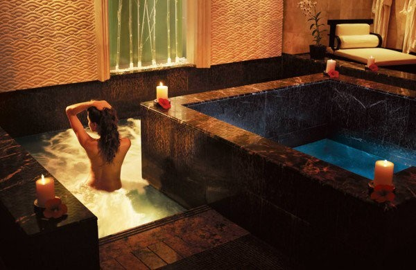 A woman relaxes in a candlelit hot tub at Mandara Spa.